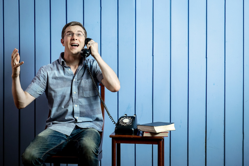 Young Caucasian Man Talking to Someone by Vintage Retro Telephone on Blue Background.