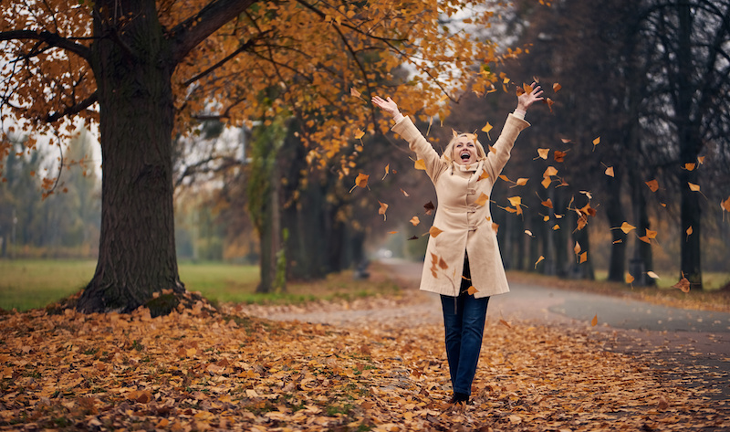 Attractive senior woman is walking in park in autumn.