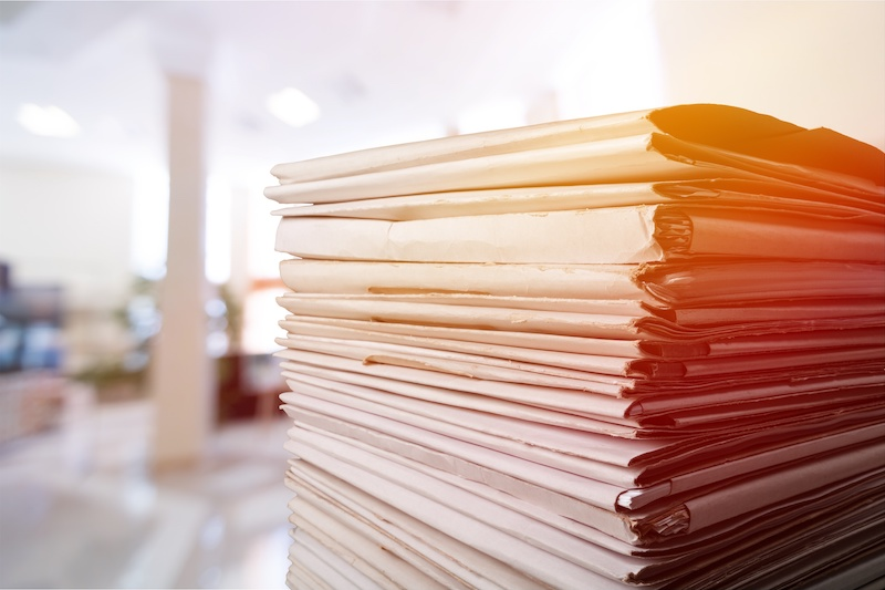 Stack of papers sitting on a desk in a court office.