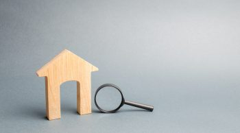 Wooden house and magnifying glass. Property valuation. Home appraisal.