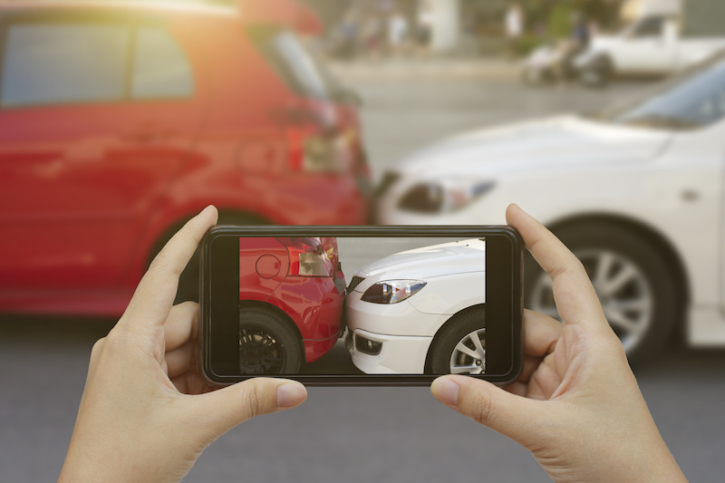 Man taking pictures of a traffic accident using his phone.