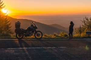 girl in full motorcycle equipment, stands on the side of the road over a cliff and looks into the distance at beautiful sunset in the mountains