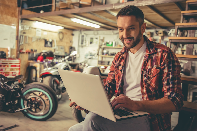 Handsome man in casual clothes is using a laptop and smiling while sitting in the motorcycle repair shop