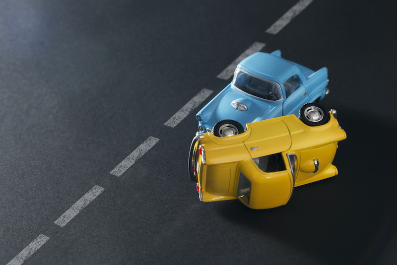 Traffic accident by two toy cars blue and yellow on a black background with road lanes.