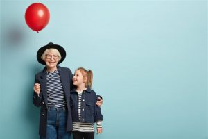 Indoor shot of fashionable senior woman embraces little child, enjoy spending time together, celebrate first day at school, hold air balloon, pose over blue background with blank space on right