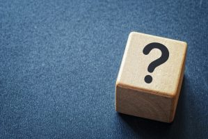 Wooden toy cube with a question mark viewed high angle on a textured blue background with copy space in a conceptual image