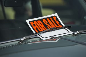 For Sale sign in a damaged car