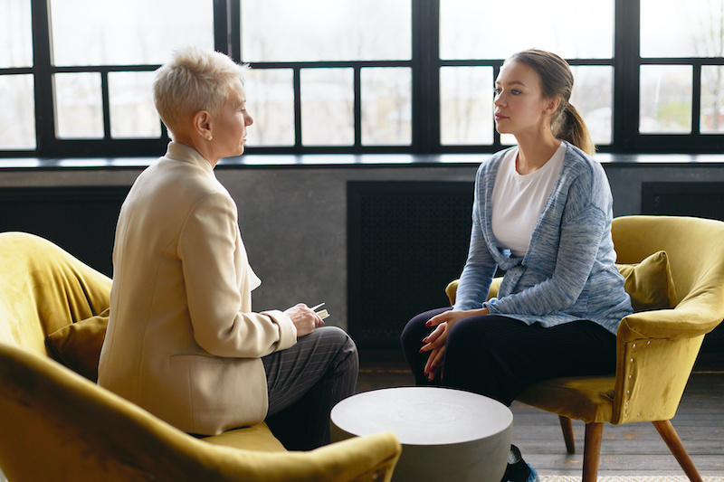 Side view image of two women sitting face to face in comfortable armchairs. Stylish mature psychotherapist conducting counseling.