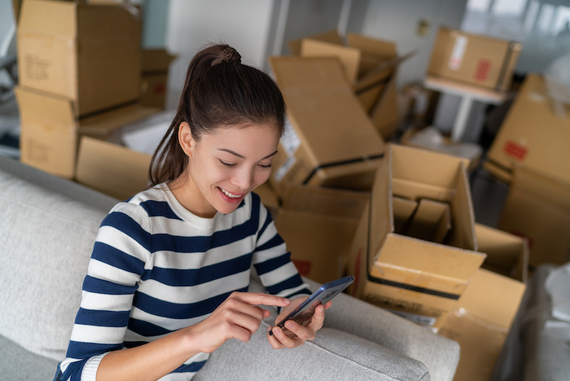 Young woman using her cellphone while settling into her new apartment.