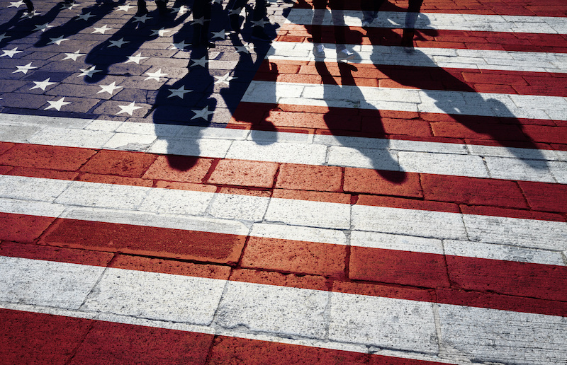 Shadows of group of people walking through the streets with painted USA flag on the floor.