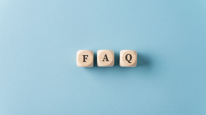 Three wooden dices spelling FAQ over light blue background.