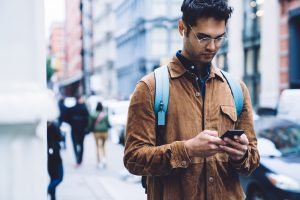 Man on his phone while walking down a sidewalk in NYC.