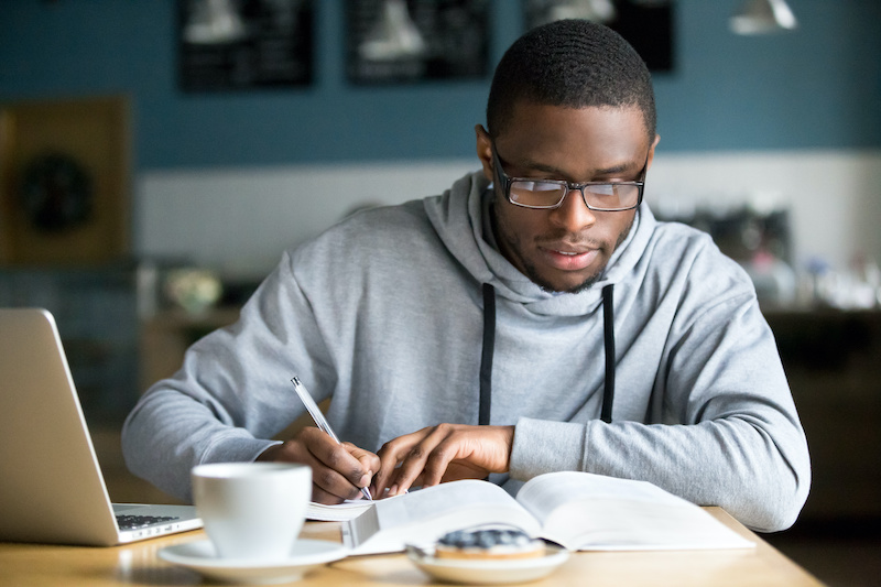 Focused millennial student in glasses making notes writing down information from book