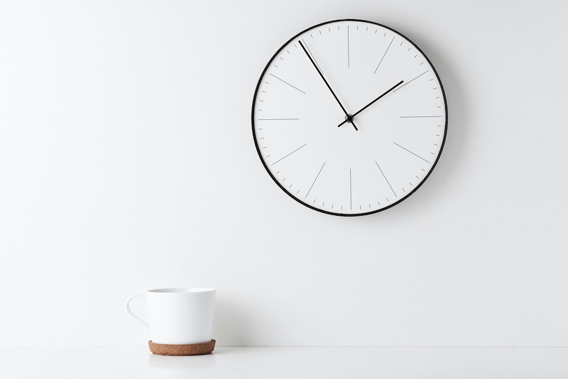Front view desk with round wall clock and cup on white background. Home office minimal workspace desk