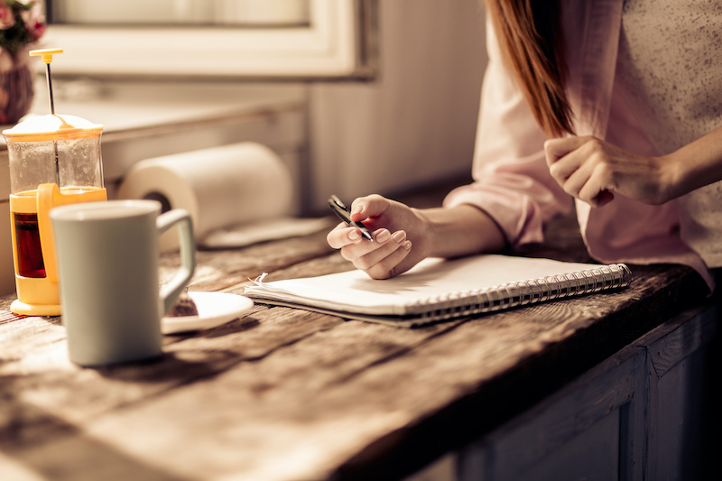 Young woman at home having coffee and making a preparedness plan