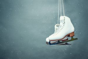 Figure skates are suspended against the background