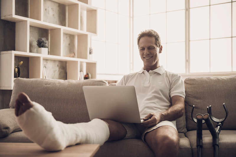 Man With Fractured Leg Sit On Sofa and Use Laptop.