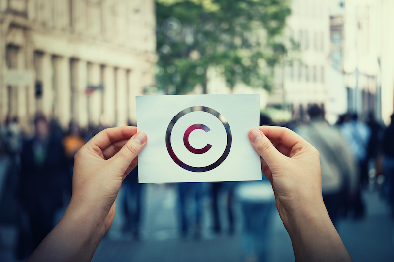 Man holding up a piece of paper with the copyright symbol on it international copyright concept