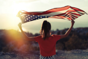 woman waving American flag on top of mountain at sky background. Sunset time