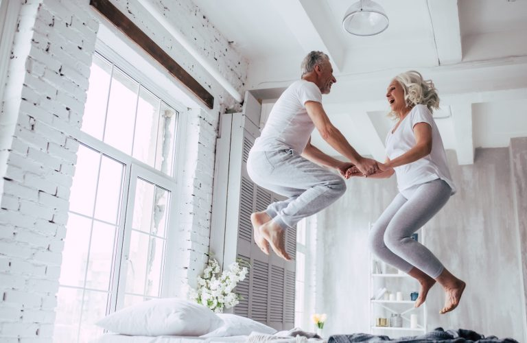 Senior couple happy and jumping on a bed during retirement.